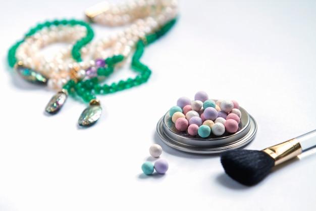 Cosmétiques et bijoux de perles sur fond blanc