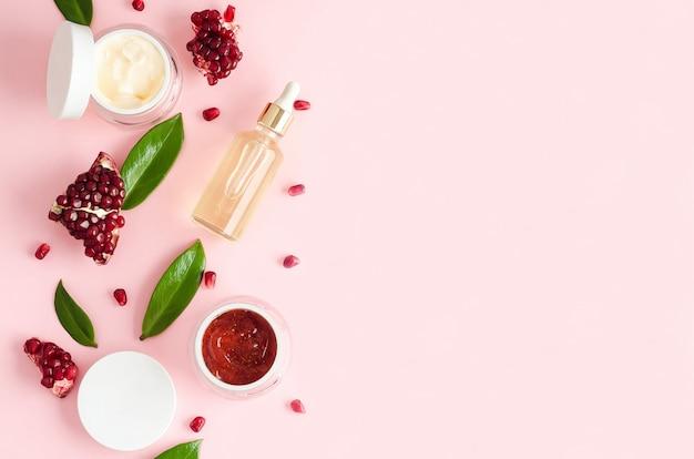 Cosmétiques biologiques naturels avec des acides de fruits aha, extrait, huile de grenade sur fond rose. concept de beauté. bouteille, pot de crème, masque, gommage, peeling pour les soins de la peau du visage. espace de copie, flou