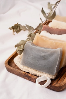 Cosmétiques biologiques naturels. pile de savon fait main dans un plateau en bois sur fond blanc