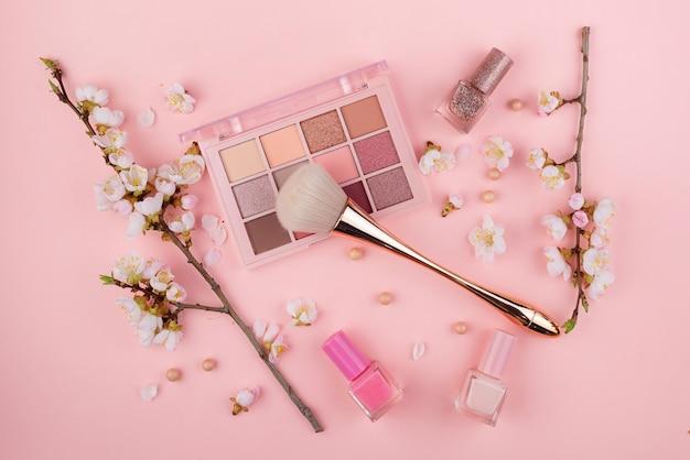 Cosmétiques et branche sakura sur un mur rose. concept de beauté, mise à plat.