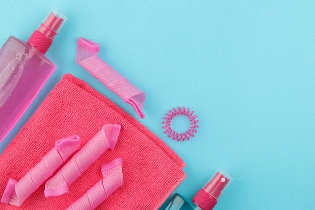 Cosmétiques capillaires et accessoires pour cheveux, bigoudis, peignes, barrettes et élastiques. sur un fond bleu clair. produits de soins capillaires. vue de dessus avec un espace pour le texte