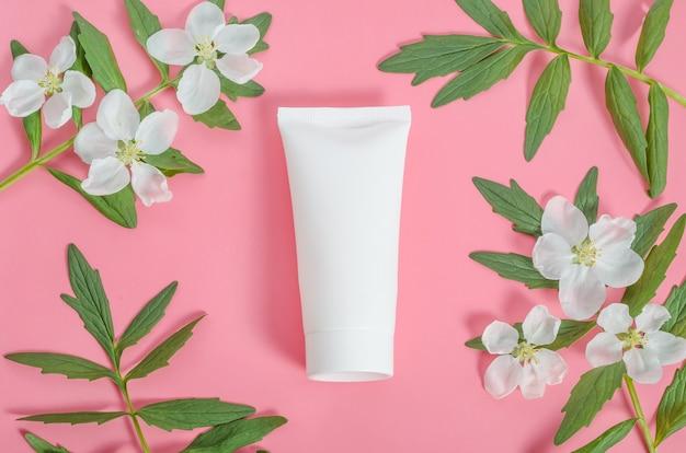 Cosmétiques comme cadeau pour la saint valentin, tube blanc de crème avec un cadre de fleurs et de feuilles sur fond rose