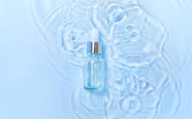 Cosmétiques dans une bouteille dans l'eau, concept d'hydratation de la peau. acide hyaluronique. mise au point sélective. la nature.