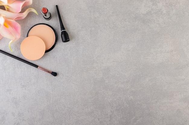Cosmétiques décoratifs et pinceaux de maquillage placés sur une table en pierre.