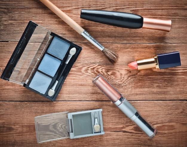Cosmétiques féminins pour le maquillage sur une table en bois. ombres cosmétiques, pinceau de maquillage, rouge à lèvres fard à paupières. mise à plat, vue de dessus.