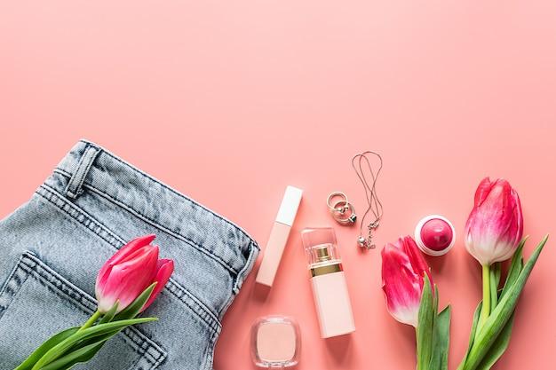 Cosmétiques filles brillantes, jeans et accessoires sur fond rose tendance