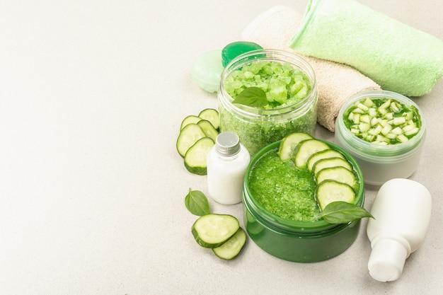 Cosmétiques maison au concombre. masques végétaux détoxifiants pour la peau. crème naturelle, sel de mer, lotion pour le corps et savon. fond de béton clair en pierre, espace de copie