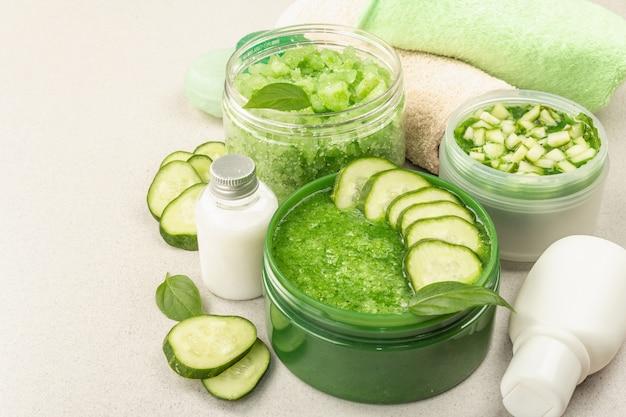 Cosmétiques maison au concombre. masques végétaux détoxifiants pour la peau. crème naturelle, sel de mer, lotion pour le corps et savon. fond de béton clair en pierre, gros plan