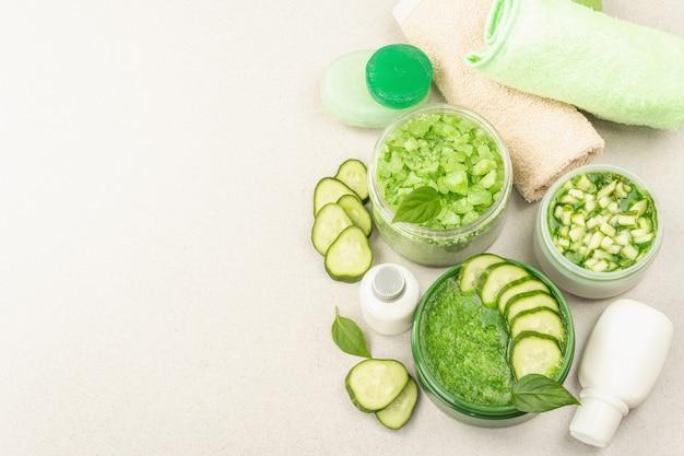 Cosmétiques maison au concombre. masques végétaux détoxifiants pour la peau. crème naturelle, sel de mer, lotion pour le corps et savon. fond de béton en pierre clair, vue de dessus