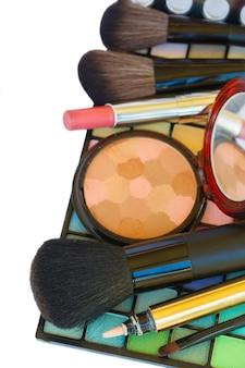 Cosmétiques de maquillage colorés décoratifs - rouge à lèvres, pinceaux et poudre sur la bordure de palette de fard à paupières isolé sur fond blanc