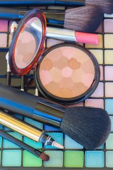 Cosmétiques de maquillage décoratifs avec poudre et pinceaux sur les ombres à paupières