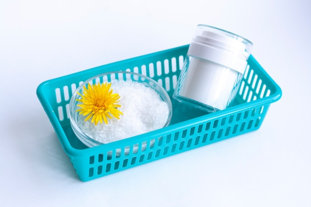 Cosmétiques naturels faits maison, sel de mer, une fleur et un pot de crème blanc dans un récipient bleu,