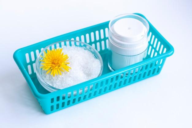 Cosmétiques naturels faits maison, sel de mer, une fleur et un pot de crème dans un récipient bleu,