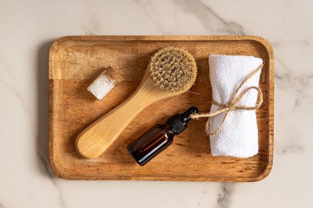 Cosmétiques naturels mis dans un emballage écologique dans un plateau en bois avec du sel de mer et une serviette. spa, produits de beauté pour le bain.
