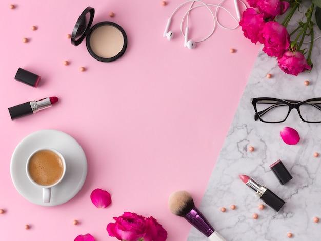 Cosmétiques, pinceaux de maquillage, rouge à lèvres, poudre et verres à fleurs sur du marbre rose tendance