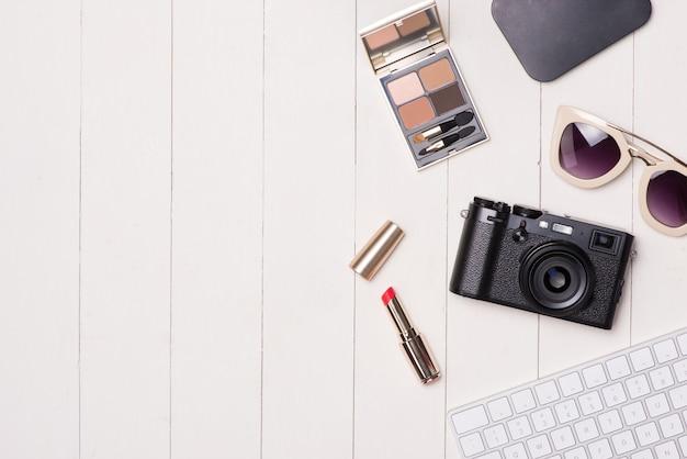 Cosmétiques pour femmes et articles de mode sur table avec appareil photo et passeport. vue de dessus