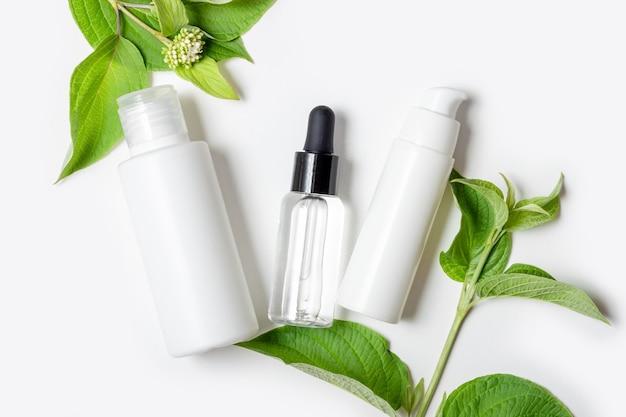 Cosmétiques pour hydrater et nettoyer le visage. eco crème et sérum pour le visage en tubes blancs et feuilles de plantes naturelles. cosmétique bio pour les soins du visage et du corps
