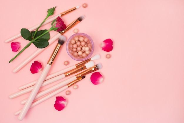 Cosmétiques pour le maquillage et les pinceaux sur une table rose