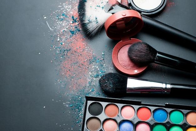 Cosmétiques pour le maquillage et les pinceaux sur un tableau noir