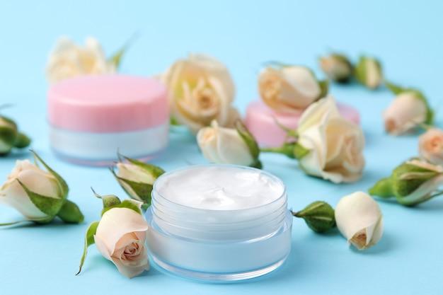 Cosmétiques pour le visage et le corps. crème dans des bouteilles roses avec des roses fraîches sur un fond bleu doux. crèmes et lotions. spa.