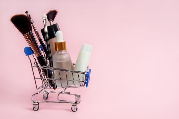 Cosmétiques de soin et pinceaux de maquillage dans un panier d'épicerie sur fond rose