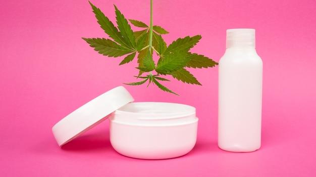 Cosmétiques de soins de la peau à l'extrait de marijuana sur fond rose, crème rajeunissante à la feuille de cannabis.