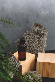 Cosmétiques spa dans des bouteilles en verre brun sur fond naturel de mousse, bois, écorce d'arbre et fougère.