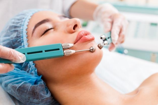 Cosmétologie. belle femme à la clinique de spa recevant un traitement facial électrique stimulant du thérapeute.