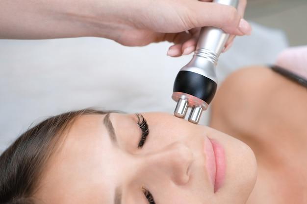 Cosmétologie matérielle. jeune femme obtenant une procédure de lifting du visage rf dans un salon de beauté.
