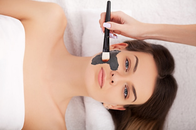 Cosmétologie matérielle. photo gros plan de la belle jeune femme avec un masque de crème dans un salon de beauté.