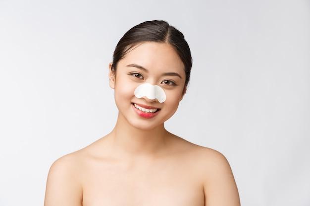 Cosmétologie. portrait de beau modèle féminin asiatique avec masque sur le nez. gros plan d'une jeune femme en bonne santé avec une peau douce et pure et un maquillage naturel frais.