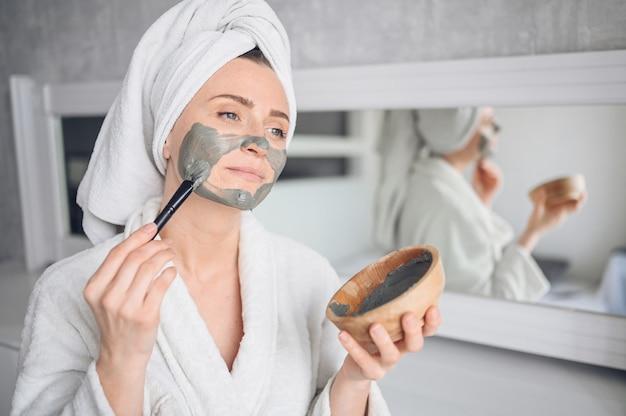 Cosmétologie, soins de la peau, soins du visage, spa, concept de beauté naturelle. belle femme souriante à la maison en peignoir avec une serviette appliquant un masque à l'argile pour le visage contre l'acné pour rajeunir la peau à problème