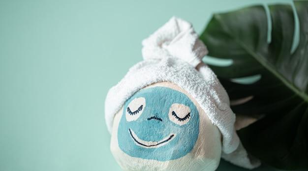 Cosmétologie, soins de la peau, traitement du visage, spa et concept de beauté naturelle. noix de coco avec masque facial créatif et serviette sur le dessus