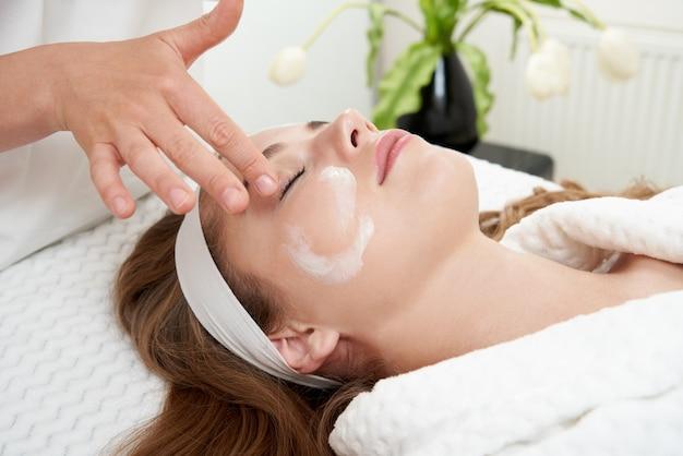 Cosmétologue appliquant de la crème sur le visage d'une femme ayant un soin du visage dans un salon de spa