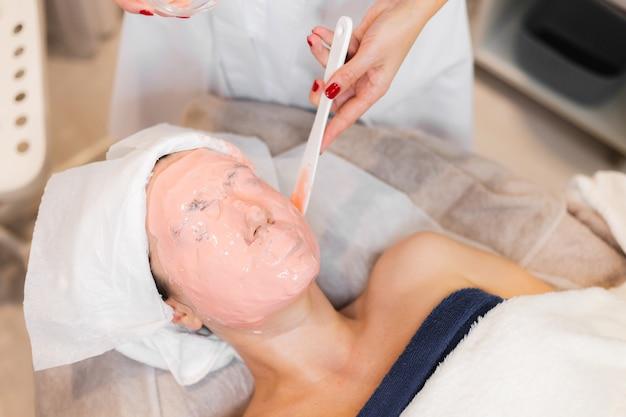 Le cosmétologue applique un masque d'alginate avec une spatule sur le visage de la femme.