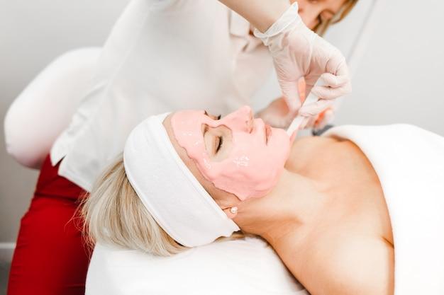 La cosmétologue applique un masque sur le visage du client