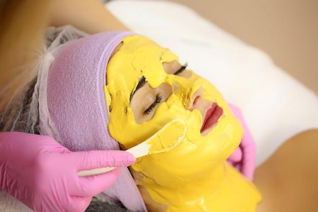 Cosmétologue appliquer un masque facial dans un salon de beauté.