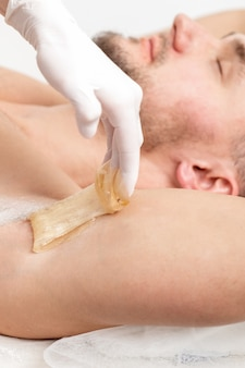 Cosmétologue, appliquer de la pâte de cire sur l'aisselle masculine