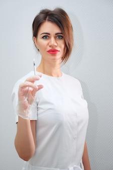 Une cosmétologue attirante avec des lèvres rouges charnues se tient debout et tient une seringue remplie d'acide hyaluronique