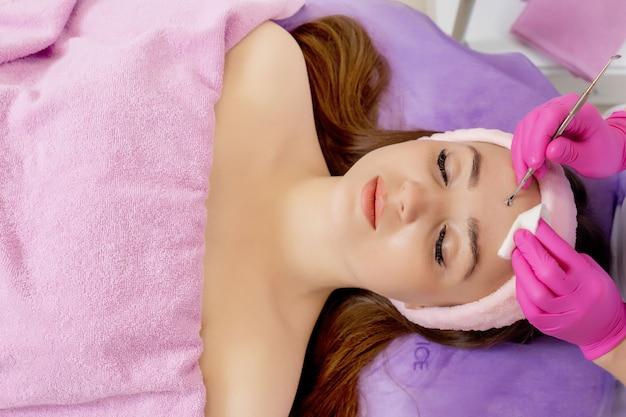 Cosmétologue au salon de beauté spa faisant le traitement de l'acné à l'aide d'un instrument mécanique