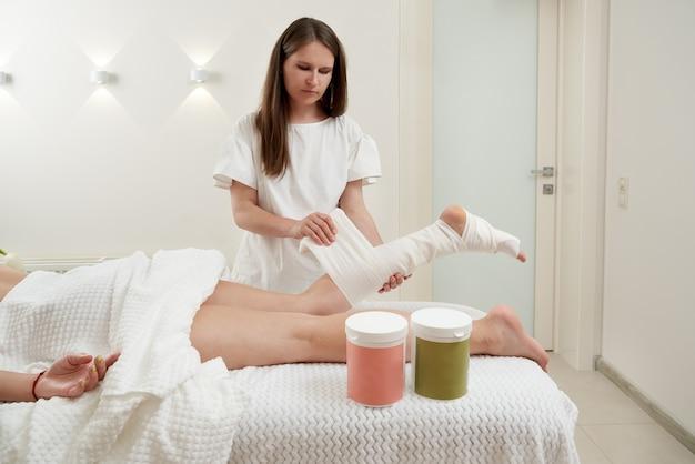 Le cosmétologue enveloppe la jambe de la procédure anticellulite du client d'emballage et de banderolage du styx