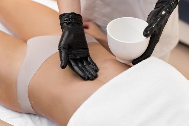 Cosmétologue faisant un massage anti-cellulite et une desquamation de l'abdomen avec du sel
