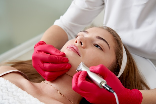 Cosmétologue faisant le nettoyage du matériel du visage du beau nettoyage de la peau du concept de jeune patient