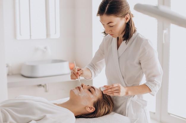 Cosmétologue faisant un traitement du visage et appliquant un masque facial