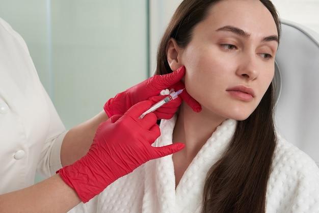 Le cosmétologue fait des injections lipolytiques pour brûler les graisses sur le menton contre le double menton.