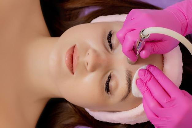 Le cosmétologue fait la procédure microdermabrasion de la peau du visage d'une belle jeune femme dans un salon de beauté. cosmétologie et soins de la peau professionnels.