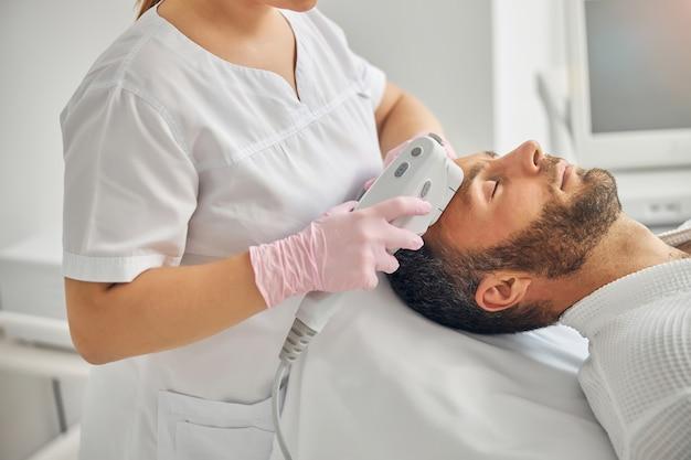 Cosmétologue féminine dans des gants stériles à l'aide d'un appareil laser ipl lors de l'exécution d'une procédure de soins de la peau pour un client masculin