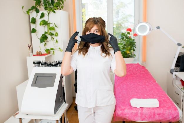 Cosmétologue femme mettant un masque de protection noir dans une clinique de beauté