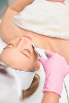 Cosmétologue gros plan faisant le nettoyage du visage par ultrasons