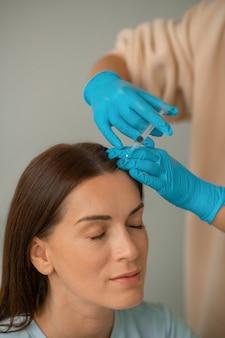 Cosmétologue injectant du collagène au visage de ses clients